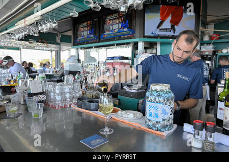 Male bartender pouring a glass of white wine at Bud and Alley's Bar and Grill rooftop restaurant in Seaside Florida, USA. - Stock Image