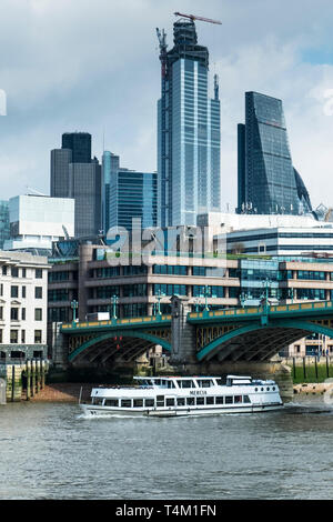 The tourist sightseeing boat Mercia passing under Southwark Bridge on the River Thames with the iconic high rise buildings in the background. - Stock Image