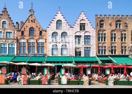 Old buildings now cafes and restaurants with ornate gables in the Historic square the Markt in the centre of Bruges Belgium West Flanders EU Europe - Stock Image