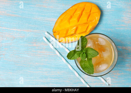 mango ice tea with mint in a glass  on  blue  wooden background (top view ) - Stock Image
