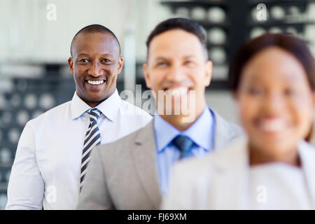 happy African businessman standing in a row with business team - Stock Image