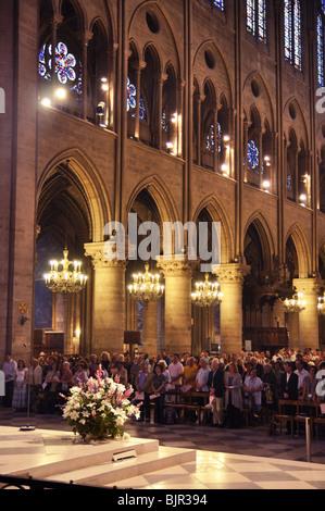 People pray inside Notre Dame de Paris, France - Stock Image