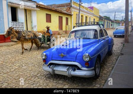 Old Man in Horse Carriage and Classic Cuban Taxi Car, showing contrasting Transport Modes and typical City Life in Trinidad, Cuba - Stock Image