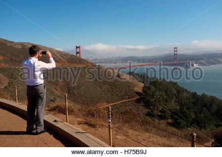 Man using his mobile phone to photograph the Golden Gate Bridge, from the north side, in Marin County, California, - Stock Image