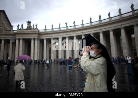 A tourist takes a picture in the rain in Saint Peter's Square in Vatican City, Rome, March 10, 2008. Photo/Chico - Stock Image