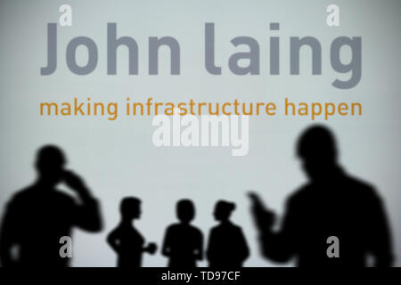 The John Laing logo is seen on an LED screen in the background while a silhouetted person uses a smartphone in the foreground (Editorial use only) - Stock Image
