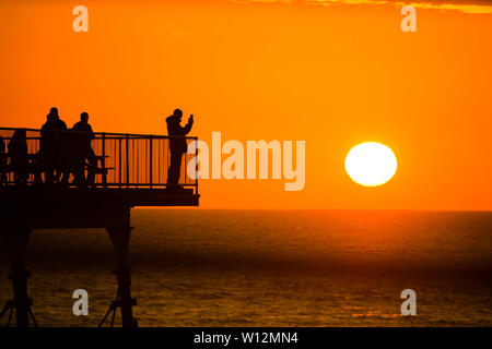 Aberystwyth, Wales, UK. Saturday 29 Jun 2019.  UK weather: At the end of a cloudy cool day in Aberystwyth, with sea mists rolling in off Cardigan Bay, the sun finally emerged, silhouetting people  stood at the end of the town's Victorian era seaside pier.  Today has been the hottest day of the summer so far in many parts of the UK, with west London experiencing temperatures of 34ºc (93.2F)  Photo credit Keith Morris/Alamy Live News - Stock Image