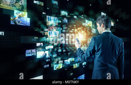 Young business man watching many pictures with smart phone. - Stock Image