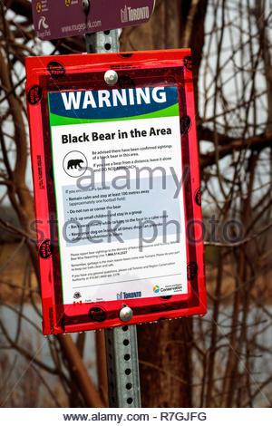 Warning sign of nuisance black bear sighting in Rouge National Urban Park an urban wilderness inside Toronto Ontario Canada - Stock Image