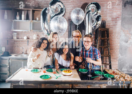 Young girl celebrates her birthday blowing out the candles with her friends,flare used to increase the mood and - Stock Image