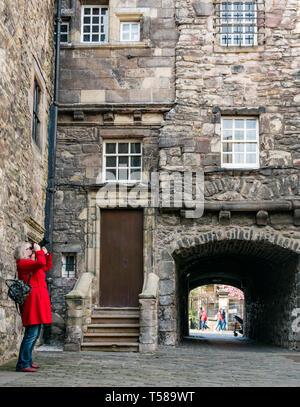 Senior woman wearing red coat taking photos of Outlander film location, Bakehouse Close, Royal Mile, Edinburgh, Scotland, UK - Stock Image