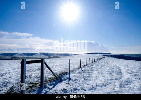 A long fence with a diminishing perspective sitting on the top of white snow covered mount Caburn, Lewes, East Sussex, United Kingdom, snow covered ro - Stock Image