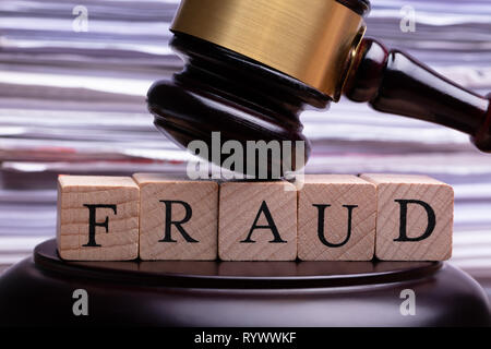 Close-up Of Wooden Gavel Striking On Wooden Block With Fraud Word Against Blurred Background - Stock Image