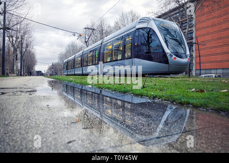 Modern tram reflecting in puddle at rainy winter morning in Toulouse, Occitanie, France - Stock Image