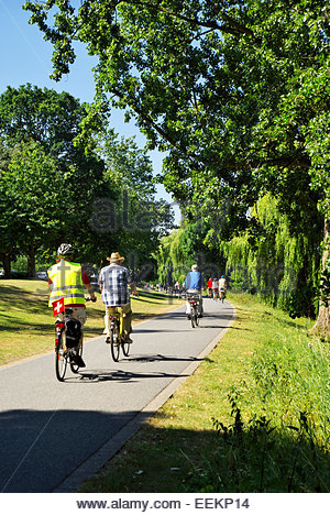 People ride bicycles and stroll on a path that runs around the Münstersche Aasee in Münster, Nordrhein - Stock Image