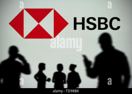 The HSBC logo is seen on an LED screen in the background while a silhouetted person uses a smartphone in the foreground (Editorial use only) - Stock Image