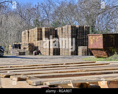 Wooden pallets are stacked high in storage waiting for use in Montgomery Alabama, USA. - Stock Image