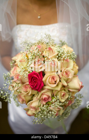 Closeup of bride holding a bouquet of roses on her wedding day. - Stock Image