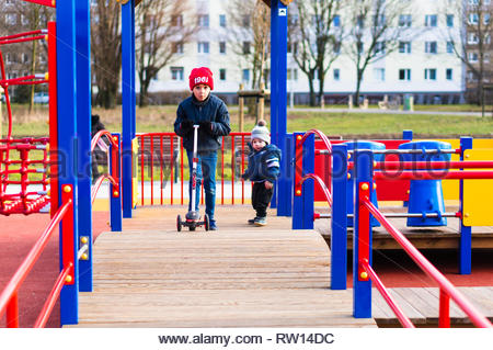 Poznan, Poland - February 24, 2019: Young boy riding a child scooter on a wooden platform of a equipment on a playground. - Stock Image