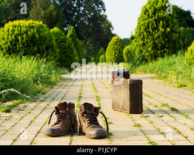 It's time to wander the world and collect memories. Shabby boots in a foreground. An analog camera on a vintage suitcase, in a blurry background. - Stock Image