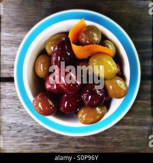 Bowl of olives with orange zest - Stock Image