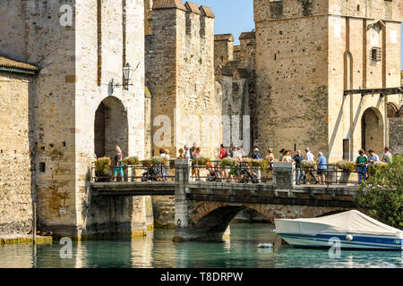 SIRMIONE, LAKE GARDA, ITALY - SEPTEMBER 2018: People crossing the bridge into the old town and Scaliger Castle in the lakeside town of Sirmione on Lak - Stock Image