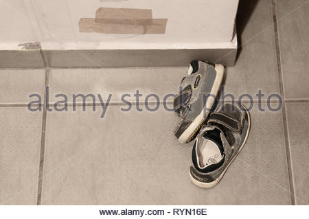 Poznan, Poland - March 8, 2019: Pair of small leather child shoes laying on a tile floor next to a wall. - Stock Image