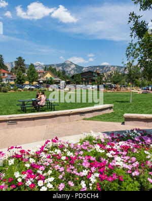 ESTES PARK, CO, USA-18 JULY 18: Two young women sit at a picnic table with bright pink flowers in the foreground, and The Rocky Mountains beyond. - Stock Image