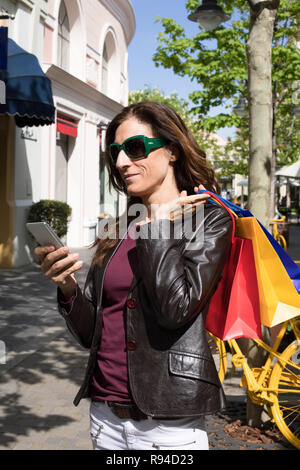brown hair woman with red shirt, leather blazer jacket and sunglasses with shopping bags on shoulder, at city street, looking at mobile smart phone - Stock Image