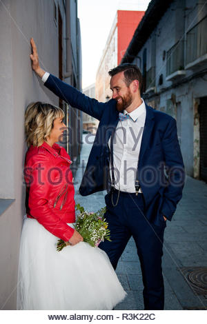 Newlywed couple poses in an alley - Stock Image