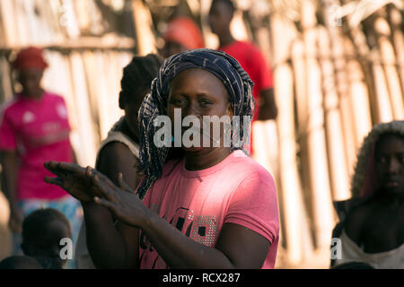 An indigenous Jola tribe woman dancing during a ritual celebration in the village of Berending, The Gambia, West Africa. - Stock Image