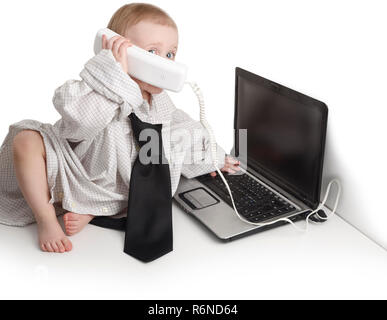 Young 1-2 year caucasian boy on phone and laptop computer dressed in business shirt and tie on white background - Stock Image