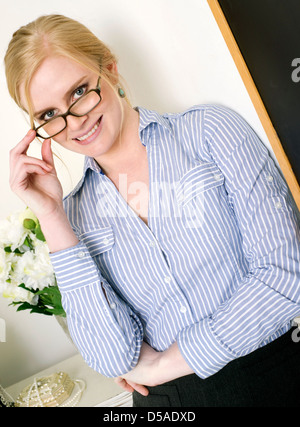 Beautiful Blond Intellectual Woman in the Field Education Stands next to Her Blackboard - Stock Image