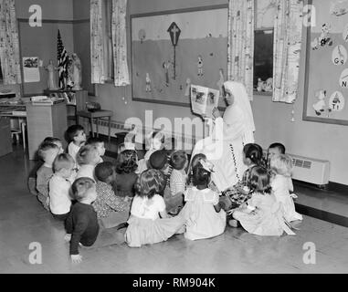 A Catholic nun teaches a classroom of first graders on Chicago's South Side, ca. 1962. - Stock Image