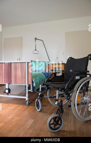 Room with nursing bed and wheelchair - Stock Image