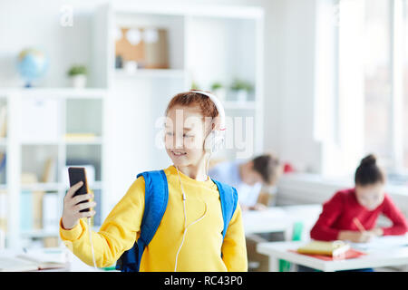 Happy little girl with backpack and headphones making selfie on smartphone in classroom - Stock Image