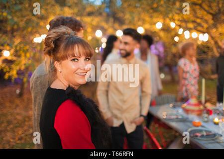 Portrait smiling woman enjoying dinner garden party - Stock Image