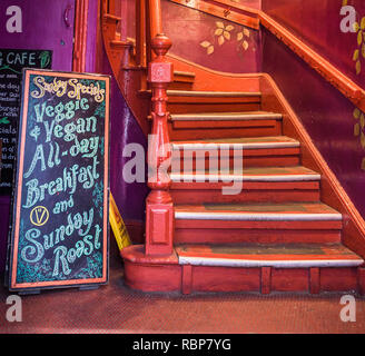 Handmade sign to a vegeterian and vegan restaurant offering a Sunday roast and all day breakfast. - Stock Image