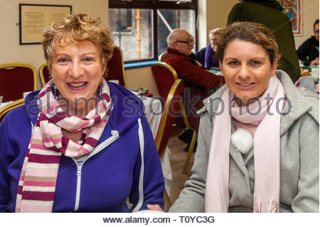 Ballydehob, West Cork, Ireland. 20th March, 2019. Despite the rain, volunteers were out collecting for the annual Irish Cancer Society's Daffodil Day in various locations around West Cork this morning. The annual fund raising coffee morning took place in Ballydehob Community Hall. Pictured at the event are Mary and Deirdre Collins from Baltimore. Credit: Andy Gibson/Alamy Live News. - Stock Image
