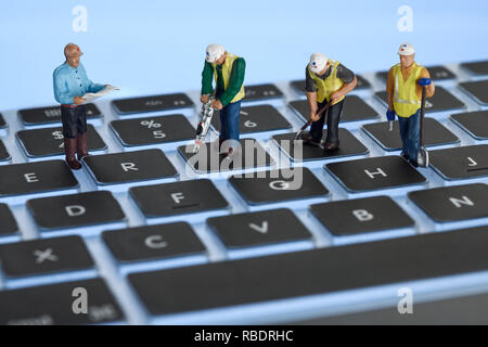 A computer keyboard with some workmen - Stock Image
