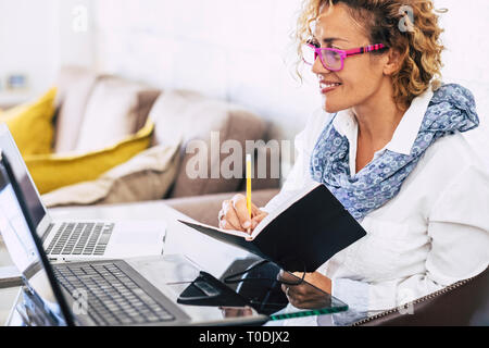 Young beautiful business woman smile and work with two different laptop - modern alternative office at home for independent people - secretary and bus - Stock Image
