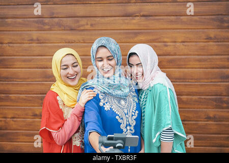 Happy muslim women making video with gimbal smart phone camera in college - Arabian young people having fun with new technology for social media - Stock Image