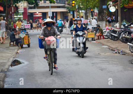 A woman wearing traditional conical straw hat rides a bicycle in the UNESCO protected town of Hoi An, Central Vietnam. - Stock Image