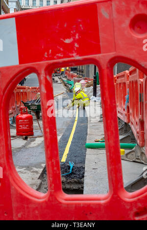 Construction workers dig up John Adam street in the West End of London to lay fibre broadband telecommunications cables. - Stock Image