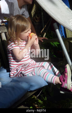 6 year old girl eating an apple - Stock Image