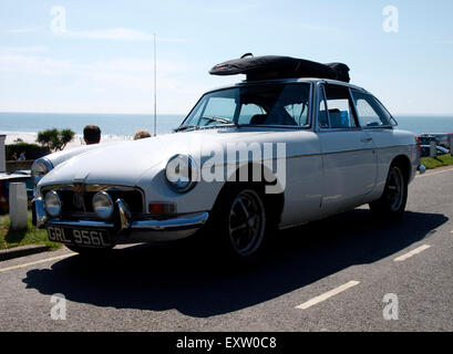 Vintage MG sports car with surfboard on the roof, Woolacombe, Devon, UK - Stock Image