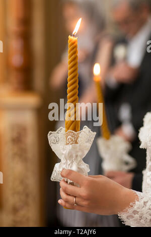 Hand of bride holding candle at wedding - Stock Image