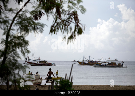 Fishermen head for their fishing boats in the evening on Mansalay Bay in Mansalay, Oriental Mindoro, Philippines. - Stock Image