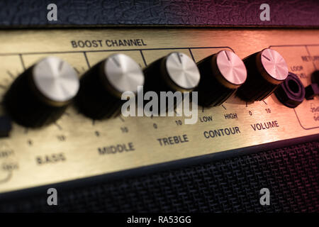 vintage amplifier five knobs diagonal closeup, magenta, isolated - Stock Image