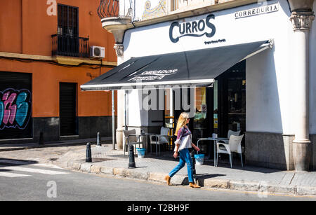 Blond woman walking passed Curros Bakery on Calle Feria in Seville - Stock Image